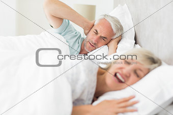 Man covering ears while woman shouting in bed