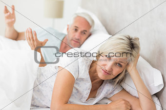 Portrait of a woman besides man in bed