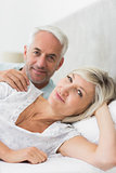 Closeup portrait of smiling mature couple lying in bed