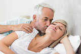 Mature man kissing womans cheek in bed