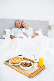 Couple sitting on bed with breakfast in foreground