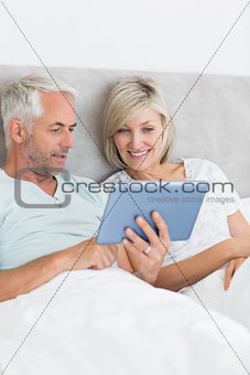 Happy couple using digital tablet in bed