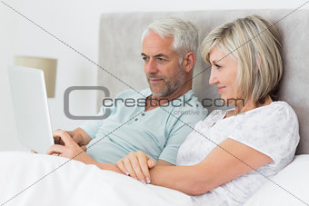 Concentrated couple using digital tablet in bed