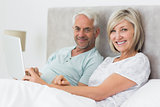 Happy mature couple using digital tablet in bed