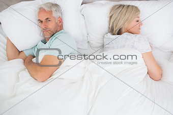Mature couple lying in bed at home