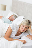 Tensed woman lying besides man in bed