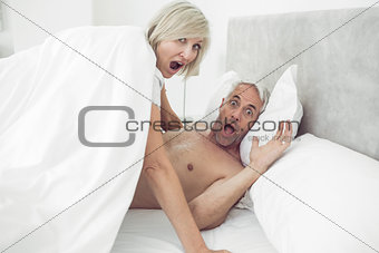 Portrait of mature couple shouting in bed