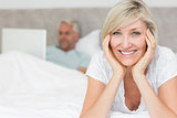 Happy mature woman with man using laptop in bed