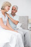 Man consoling tensed woman in bed