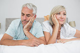 Closeup of displeased mature couple lying in bed