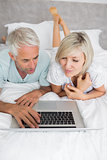 Mature couple using laptop in bed