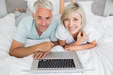 Relaxed mature couple using laptop in bed