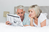 Mature couple reading newspaper in bed