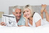 Smiling mature couple reading newspaper in bed