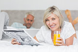 Couple reading newspaper and using laptop in bed