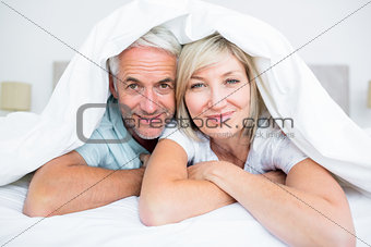 Portrait of a mature couple lying in bed