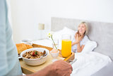 Woman sitting in bed with breakfast in foreground