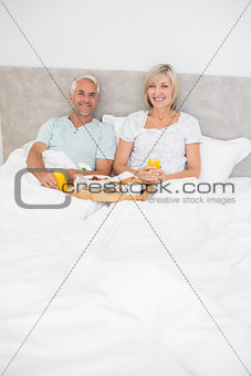 Portrait of mature couple having breakfast in bed