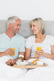 Happy mature couple having breakfast in bed