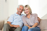Smiling mature couple sitting on sofa with arm around