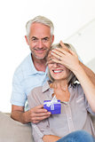Smiling mature man surprising woman with a gift