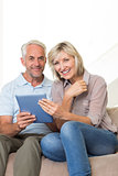 Smiling mature couple using digital tablet at home