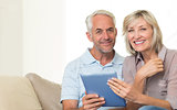 Smiling mature couple using digital tablet on sofa