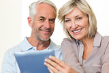 Closeup of a smiling mature couple using digital tablet