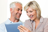 Closeup of cheerful mature couple using digital tablet