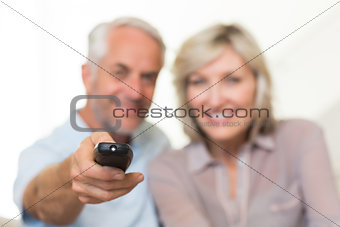 Blurred mature couple watching tv at home