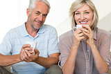 Smiling mature couple with coffee cups sitting on sofa