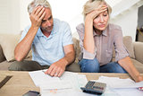 Tensed mature couple with bills and calculator at home