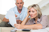 Tensed mature couple with bills at home
