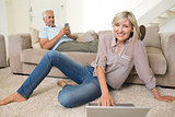 Couple with laptop and cellphone in living room at home