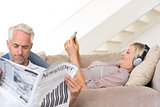 Couple with newspaper and cellphone in living room