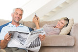Couple with newspaper and cellphone in living room at home