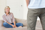 Smiling woman looking at man in living room