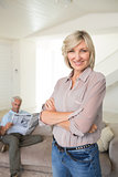 Smiling woman with man reading newspaper at home