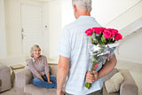 Man holding bouquet behind back with woman sitting on couch