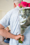 Man holding bouquet behind his back with woman sitting on couch