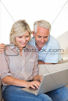 Happy mature couple using laptop on sofa