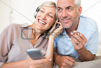 Mature couple with headphones and cellphone