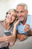 Cheerful mature couple with headphones and cellphone