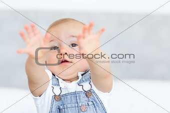 Closeup portrait of a cute baby holding out his hands