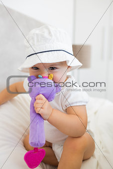 Portrait of a cute baby with toy sitting on bed