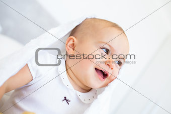 Closeup of a cheerful cute baby under comforter