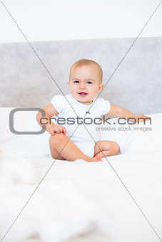 Full length portrait of cute baby sitting on bed