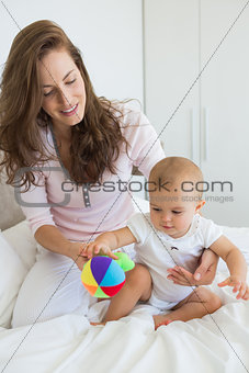 Mother and baby sitting with toy on bed