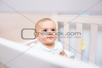 Closeup of a cute baby looking up in crib