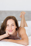 Closeup of a pretty smiling woman lying in bed